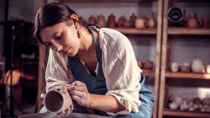Woman crafting a clay mug