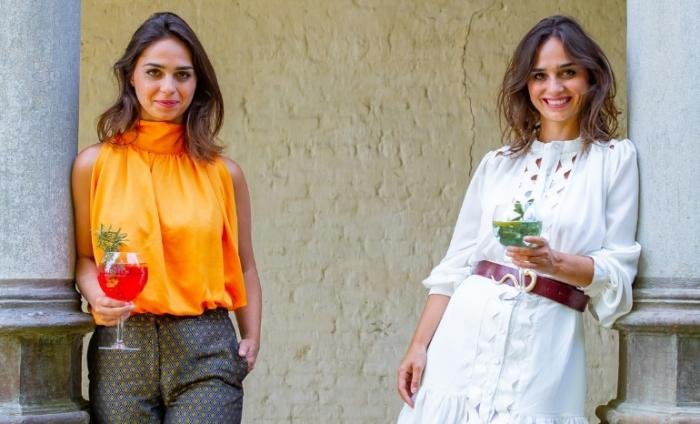 Photo of two female Double Dutch founders standing against two columns holding a glass of their tonic mixers