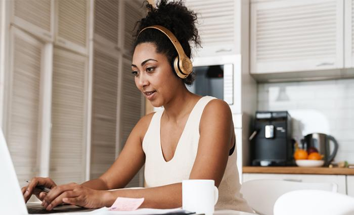 Woman working on a laptop wearing headphones in her kitchen